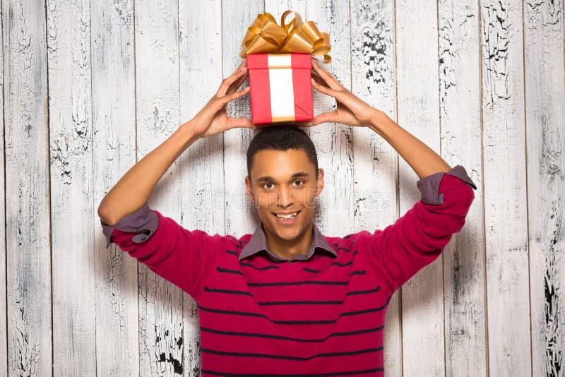 摆在与一个礼物的年轻人在演播室 免版税图库摄影