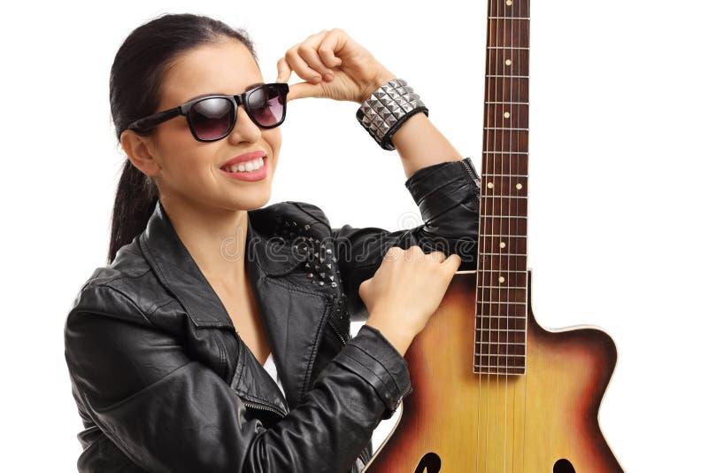 摆在与一把声学吉他的一个少妇的画象 库存照片