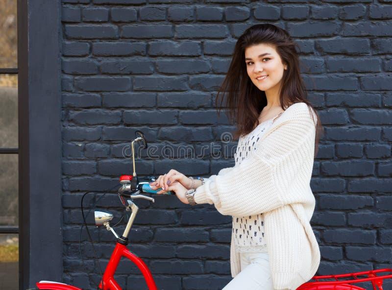 摆在与一辆时髦葡萄酒红色自行车的时髦,白色成套装备的美丽的深色的女孩户外在黑砖墙背景 免版税库存图片