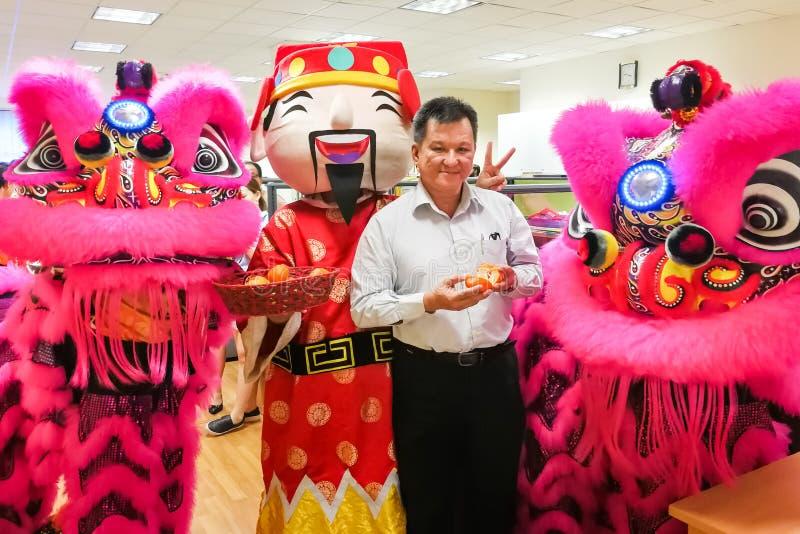 摆在与两头狮子的中国业务经理在舞蹈perfo以后 库存照片