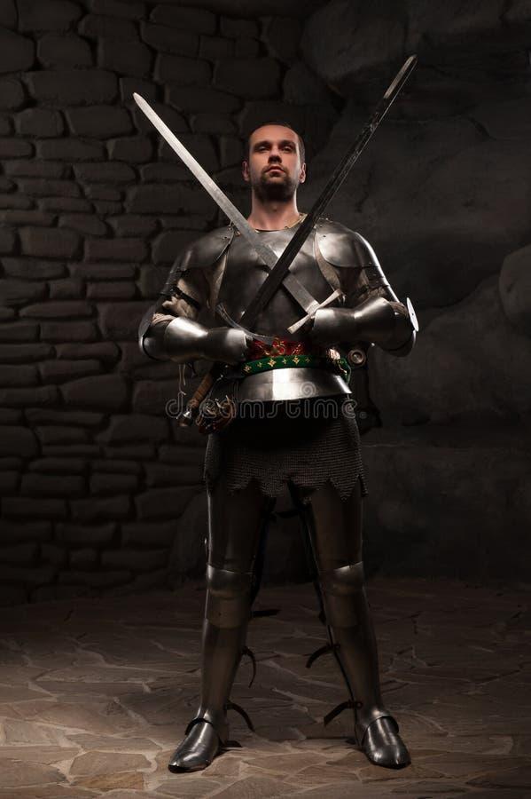 摆在与两把剑的中世纪骑士在a 免版税图库摄影