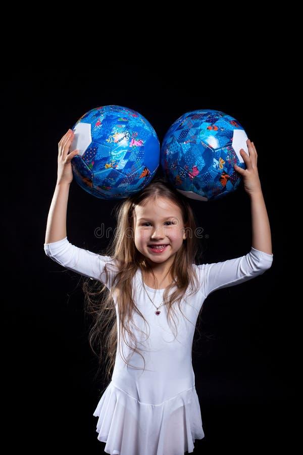 摆在与体操球的愉快的小女孩 免版税库存照片
