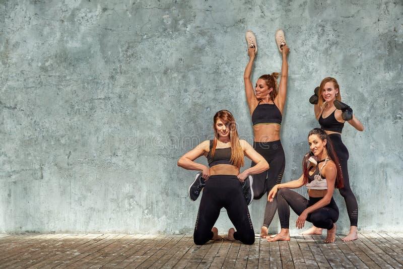 摆在与体育辅助部件的小组美丽的健身女孩对灰色墙壁 r 免版税库存图片