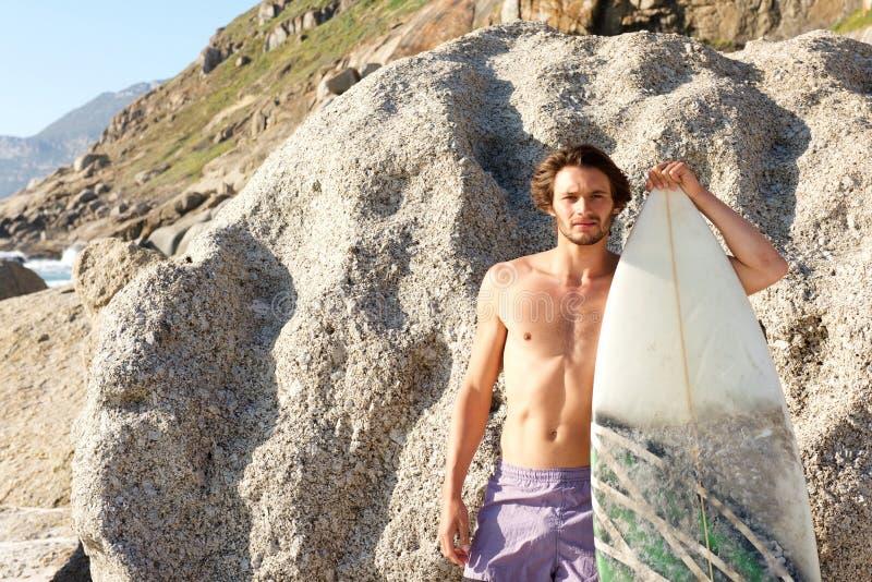 摆在与冲浪板的英俊的人在海滩 免版税库存照片