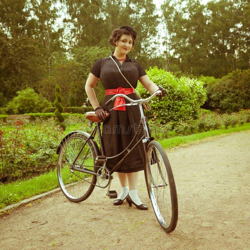 摆在与减速火箭的自行车的礼服的少妇在公园。 库存照片