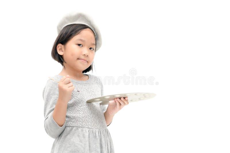 摆在与刷子和调色板的逗人喜爱的亚裔小女孩画家 免版税库存照片