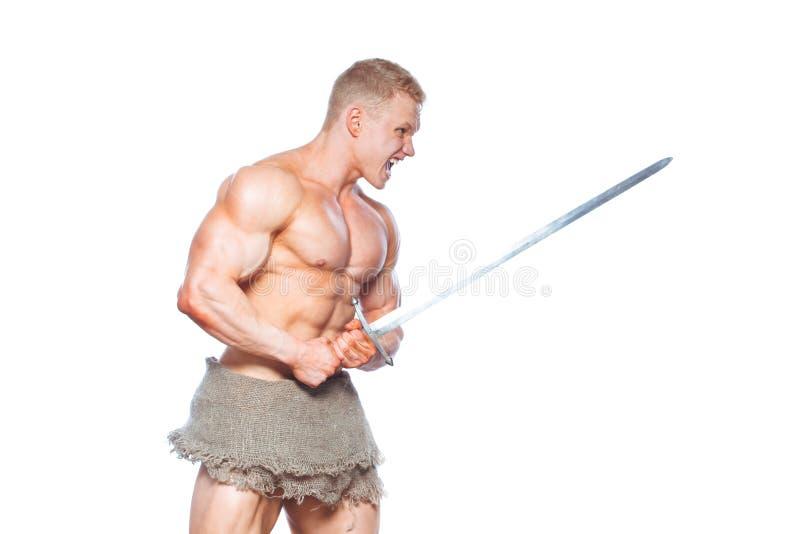 摆在与剑的爱好健美者人隔绝在白色背景 展示他的mascular身体的严肃的赤裸上身的人 免版税库存照片