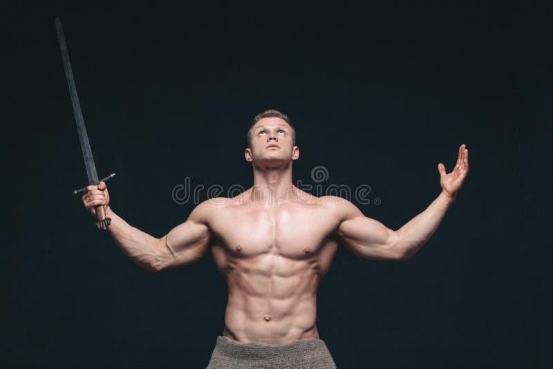 摆在与剑的爱好健美者人隔绝在黑背景 展示他的mascular身体的严肃的赤裸上身的人 免版税库存图片