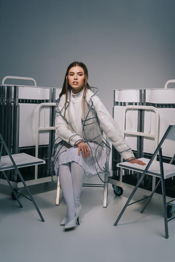 摆在与可折叠椅子的白色衣物的时髦的女人后边在灰色 库存图片