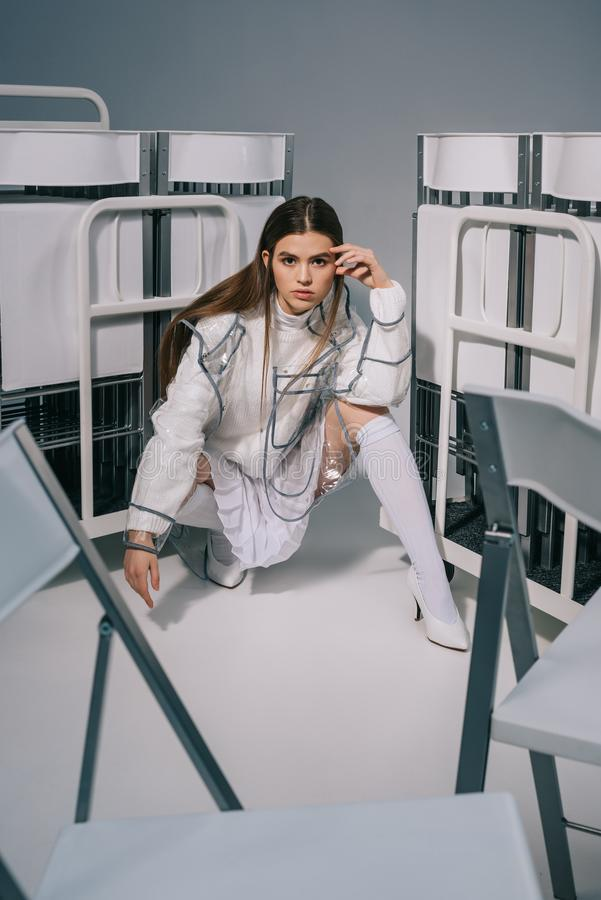 摆在与可折叠椅子的白色衣物的时髦的女人后边在灰色 免版税图库摄影