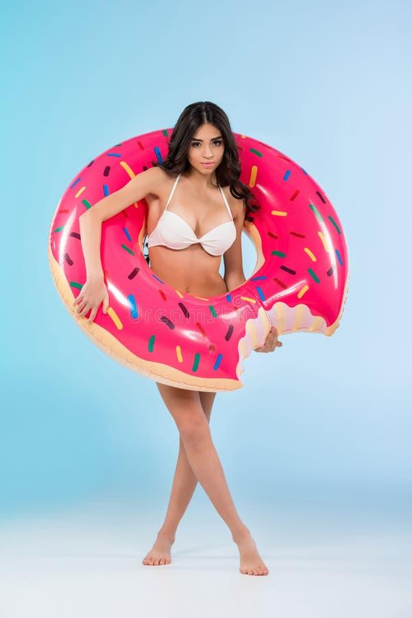 摆在与可膨胀的多福饼圆环的美丽的女孩, 免版税图库摄影
