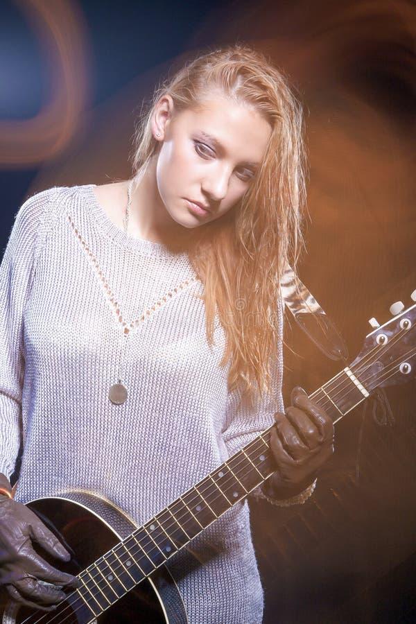 摆在与吉他的年轻白种人女性音乐播放器反对黑色 使用的闪光和卤素的组合 库存图片