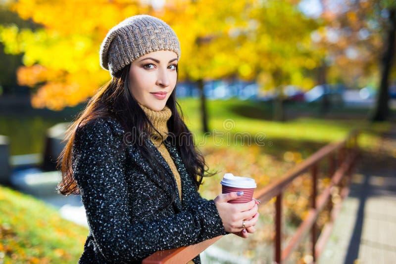 摆在与咖啡杯的年轻美丽的妇女在秋天公园 免版税库存图片