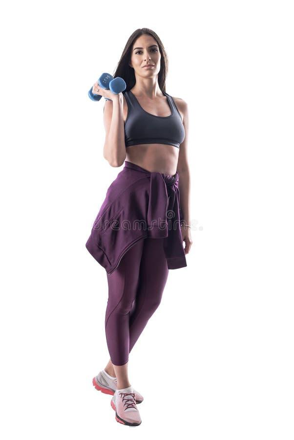 摆在与哑铃的运动的衣裳的确信的有动机的年轻健身妇女看照相机 免版税库存照片
