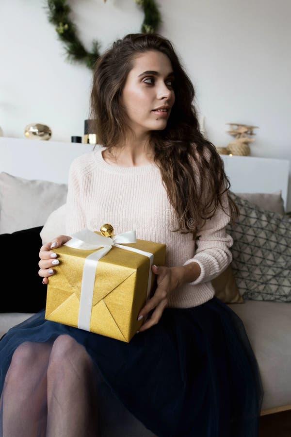 摆在与圣诞节礼物的时髦的妇女 免版税库存照片