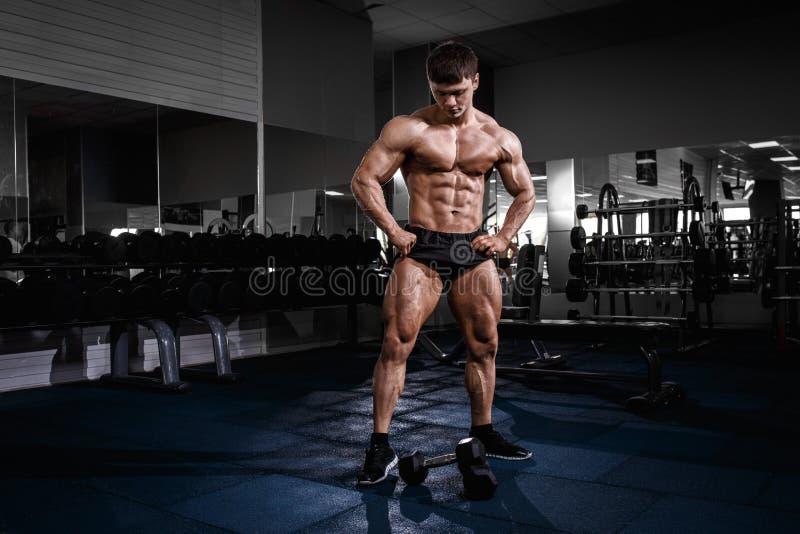 摆在与在健身房的哑铃的运动员肌肉爱好健美者人 免版税图库摄影