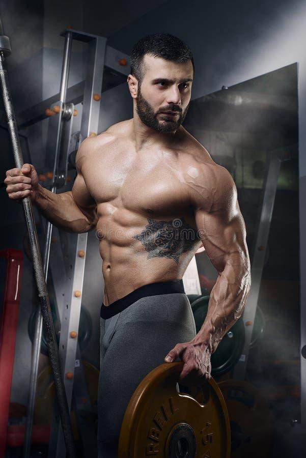 摆在与在健身房的杠铃和重量板材的肌肉露胸部的人 免版税图库摄影