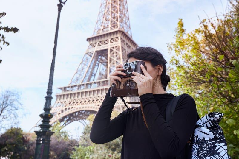 摆在与在埃菲尔铁塔的背景的一台照相机的美女 巴黎,战神广场 免版税库存图片