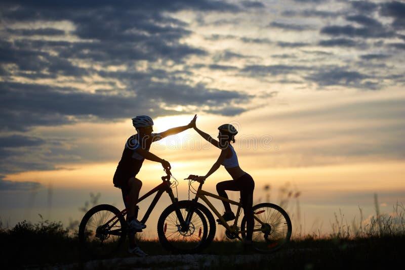 摆在与在日落的自行车的美好的夫妇 免版税图库摄影