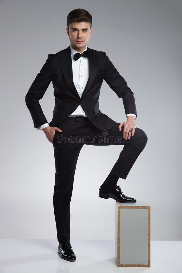 摆在与在木箱的脚的性感和轻松的商人 免版税库存图片