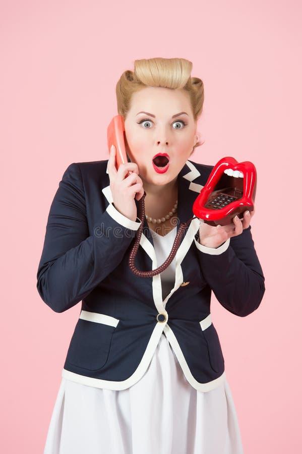 摆在与在桃红色背景的电话的情感白肤金发的卷曲发型女孩 库存照片