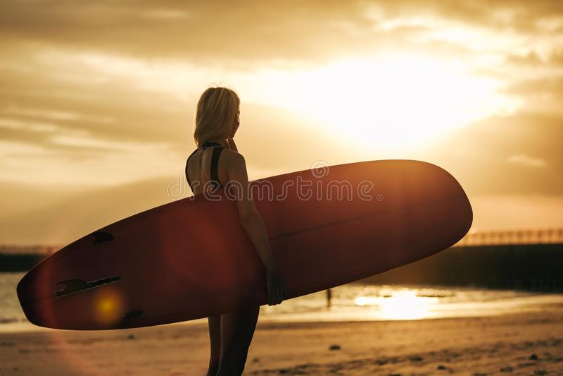 摆在与在海滩的冲浪板的冲浪者剪影在日落 免版税图库摄影