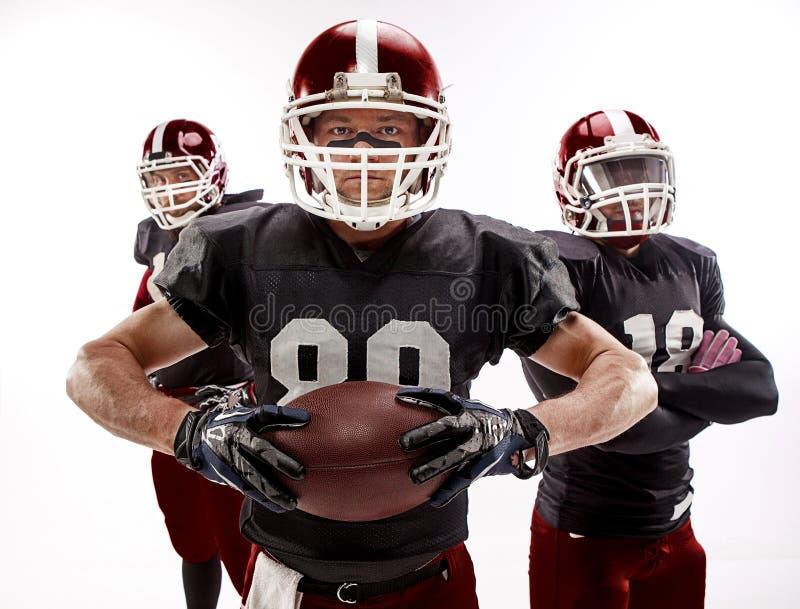 摆在与在白色背景的球的三名美国橄榄球运动员 免版税库存图片