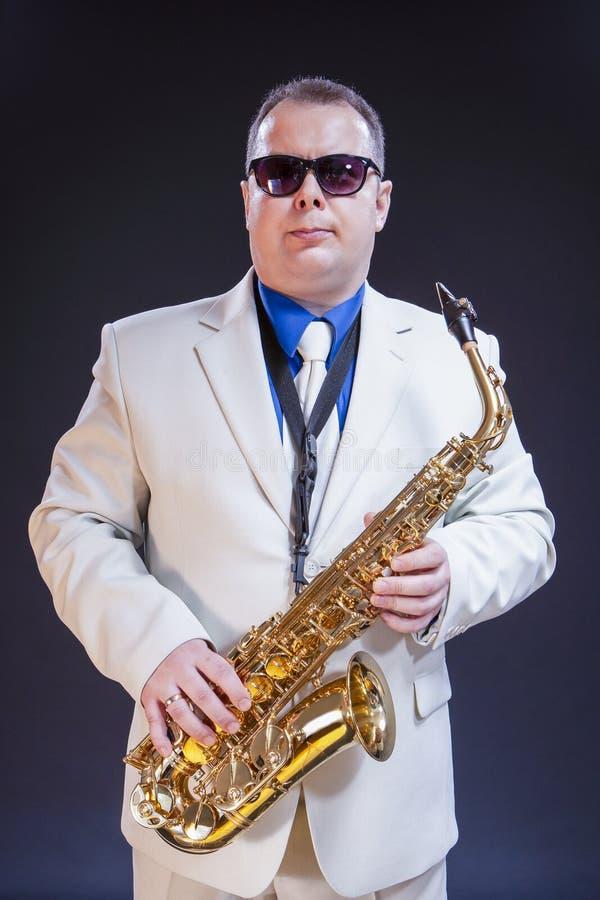 摆在与在白色衣服和太阳镜的仪器的确信的成熟男性萨克斯管吹奏者 图库摄影