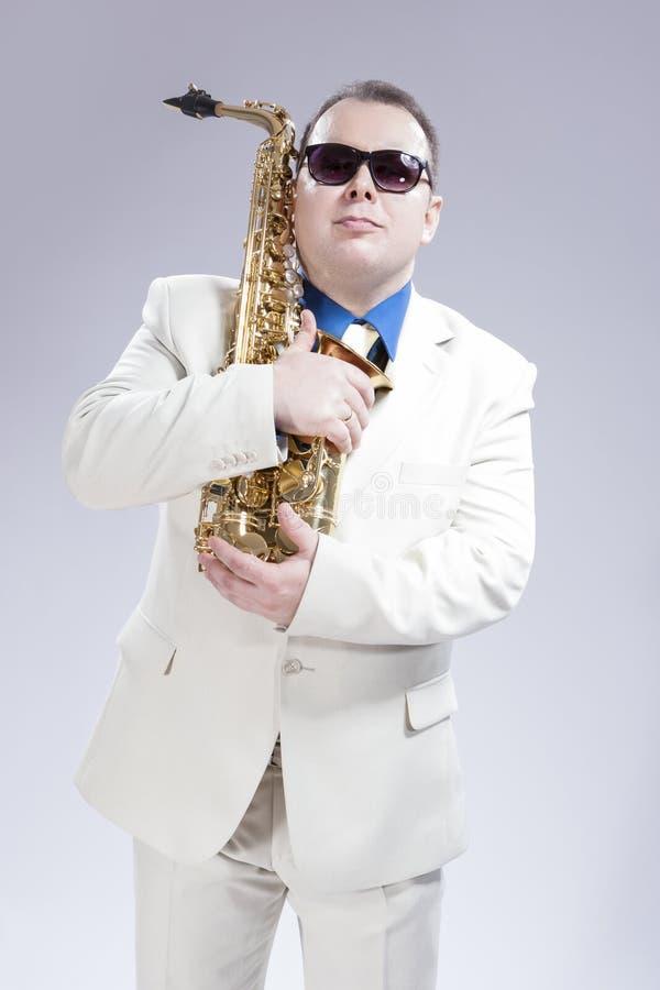 摆在与在白色衣服和太阳镜的女低音Saxo的男性萨克管演奏员 免版税库存照片