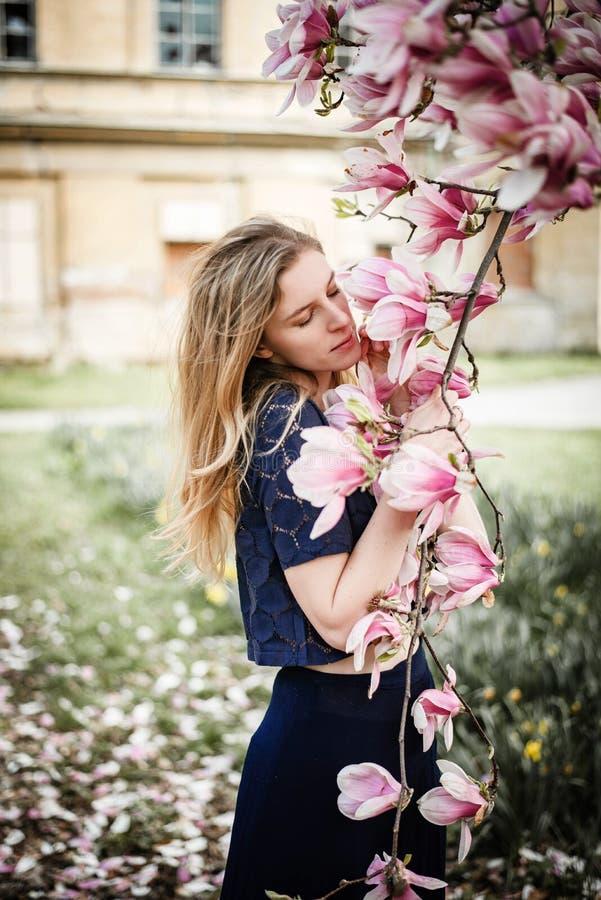 摆在与在绽放的木兰树的年轻白肤金发的妇女室外画象  库存照片