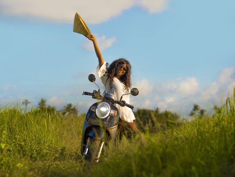 摆在与在美好的米领域的摩托车的传统亚洲帽子的年轻可爱的黑人非裔美国人的旅游妇女和 免版税库存图片