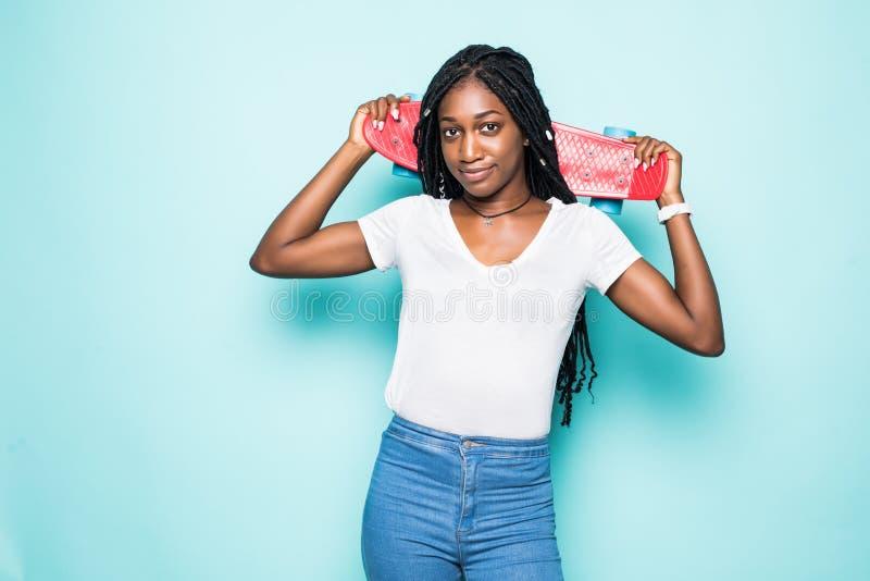 摆在与在蓝色背景的微笑的牛仔裤和白色衬衫佩带的太阳镜的惊人的年轻女人 逗人喜爱的非洲女孩藏品 库存图片