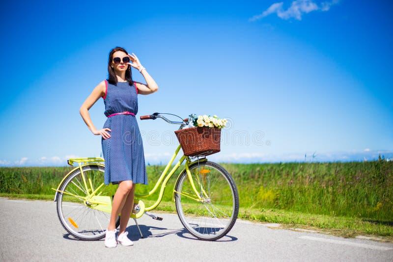 摆在与在路的减速火箭的自行车的愉快的妇女在蓝天 免版税库存照片