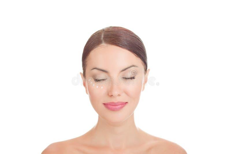 摆在与在面孔的反皱痕奶油的秀丽女孩 免版税库存照片