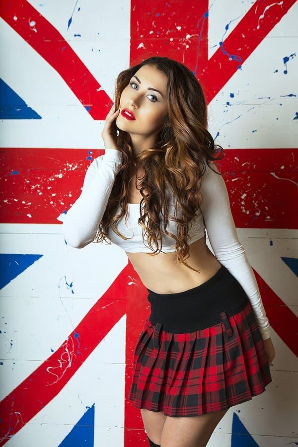 摆在与在backgr的英国旗子的美丽的逗人喜爱的少妇 免版税库存照片