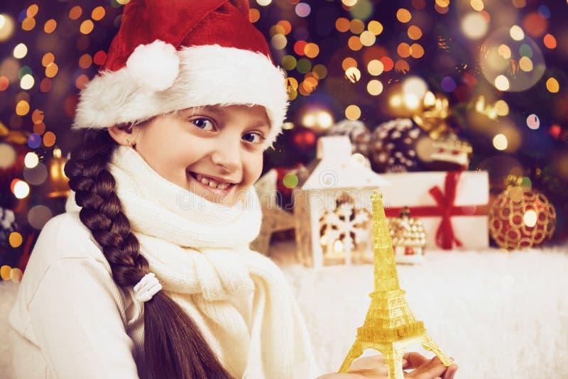 摆在与埃佛尔铁塔在黑暗的背景、被阐明的光和bokeh的玩具和圣诞节装饰的女孩孩子,面对特写镜头, d 库存图片