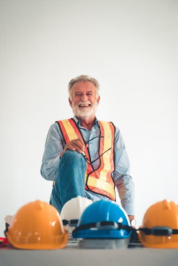 摆在与大微笑的高级工程师画象在办公室 库存图片