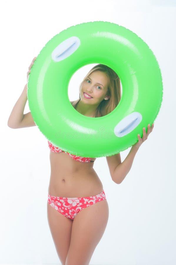 摆在与大绿色橡胶环的比基尼泳装的美丽的少妇 图库摄影