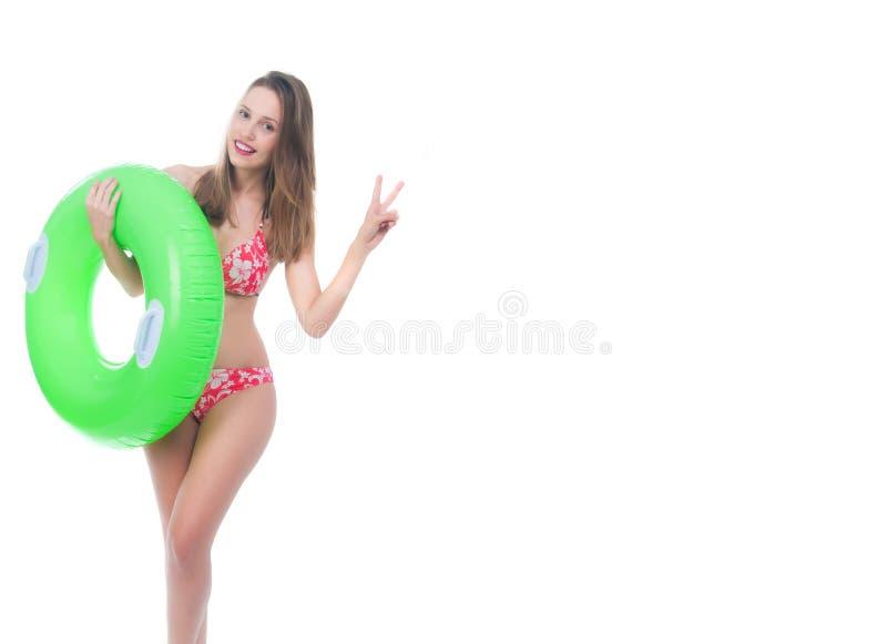 摆在与大绿色橡胶环的比基尼泳装的美丽的少妇 免版税图库摄影