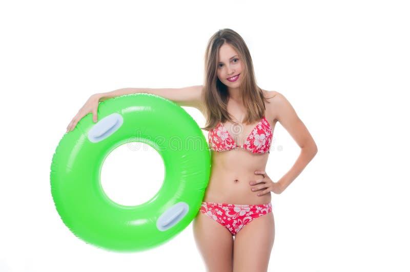 摆在与大绿色橡胶环的比基尼泳装的美丽的少妇 免版税库存照片