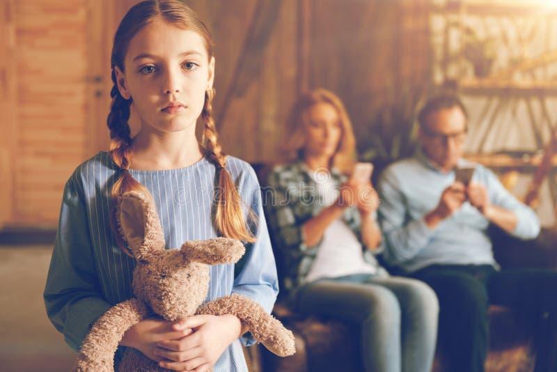 摆在与她的兔宝宝玩具的被忽略的生气孩子 库存照片