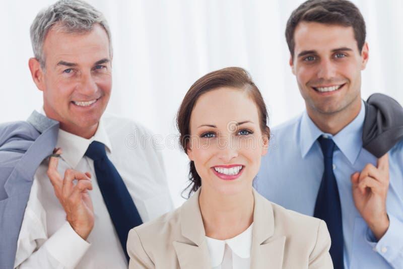 摆在与她的工作队的微笑的雇员 免版税库存图片