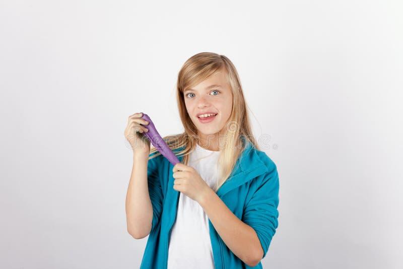 摆在与她的手工制造紫色软泥的快乐的女孩 免版税库存图片