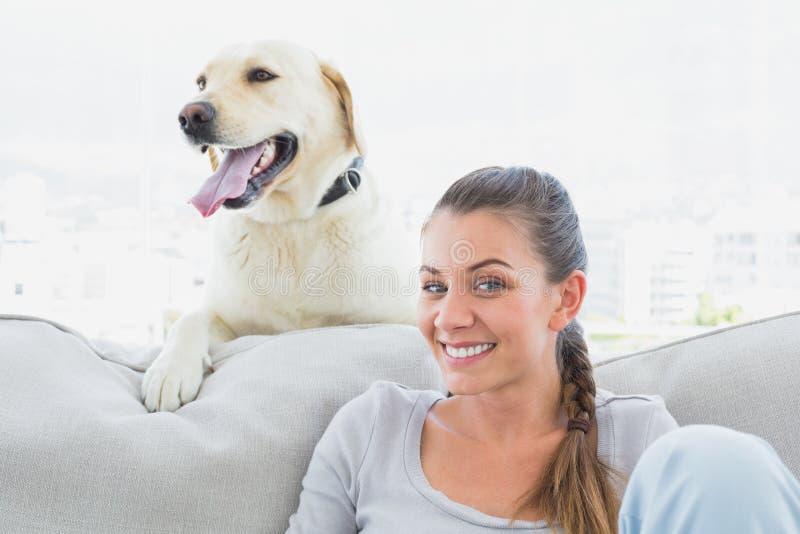 老婆与狗的情色生活_摆在与她的长沙发的黄色拉布拉多的愉快的妇女
