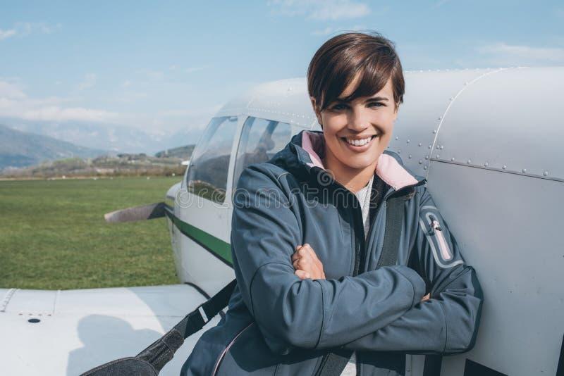 摆在与她的飞机的微笑的女性飞行员 免版税库存照片