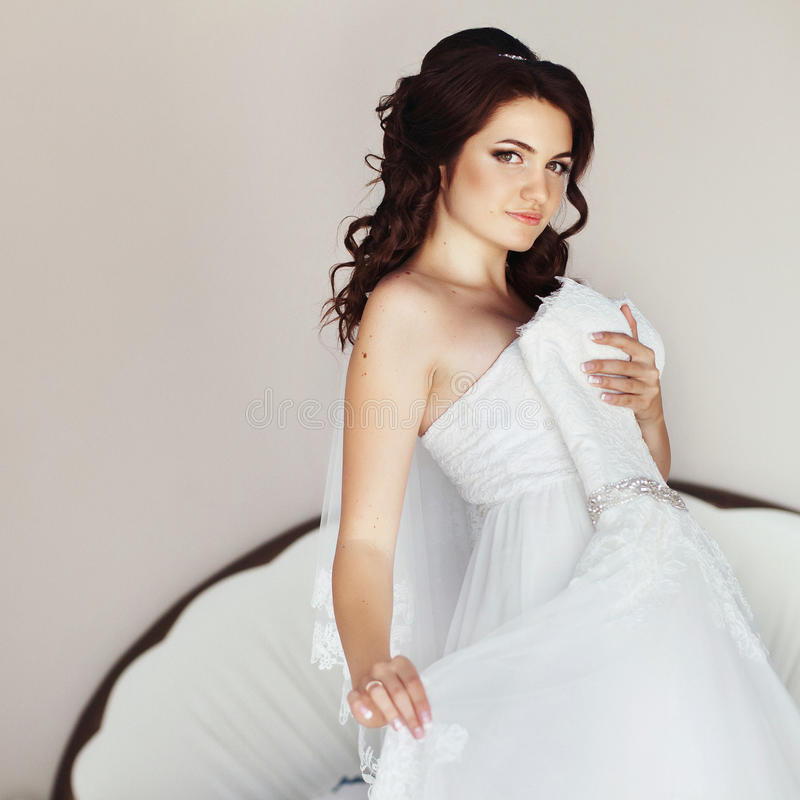 摆在与婚礼礼服的美丽的深色的新娘在屋子里 库存照片