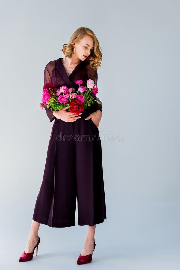摆在与嫩花的全长观点的美丽的端庄的妇女 免版税库存照片