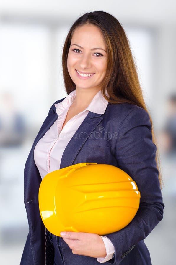 摆在与安全帽的年轻女性建筑师 图库摄影