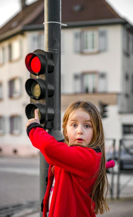 摆在与小红绿灯的逗人喜爱的小女孩 免版税库存照片