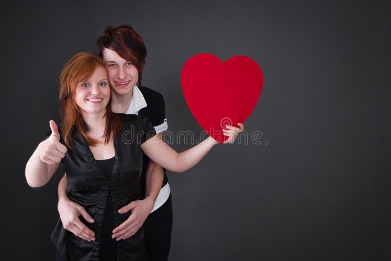 摆在与心脏-爱的夫妇 免版税库存图片